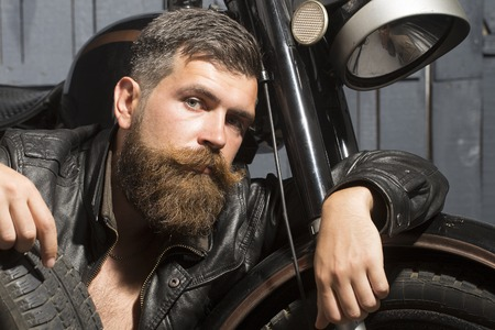 young unshaven: Young unshaven male biker in leather jacket sitting near motorcycle in garage with big black rubber spare wheel looking forward on wooden wall background, horizontal picture