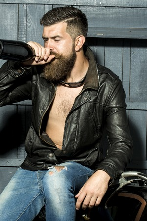motor cycle: Attractive sexy brutal male biker with long beard and moustache in brown leather jacket with open chest and blue jeans drinking from glass wine bottle sitting on motor cycle, vertical picture Stock Photo