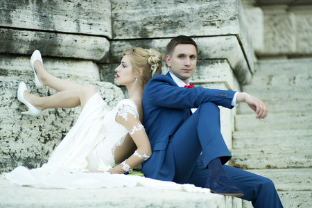lovely women: Beautiful young wedding couple of sensual blond girl in white dress and shoes and man in blue suit with red bow tie sitting near stone building outdoor, horizontal picture Stock Photo