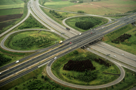 High view from plane on green landscape with beautiful round crossroads and bridges with cars driving on road onnatural background, horizontal picture