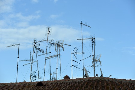 View On Tile Old Building Roof Red Color With Many Metal Rooftop Antennas  Satelites Wires And