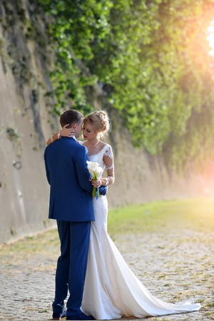 flower bunch: Beautiful young lovely wedding couple of blond woman in long white dress with calla flower bunch and man in blue suit embracing standing near stony wall with green plant sunny day, vertical photo Stock Photo