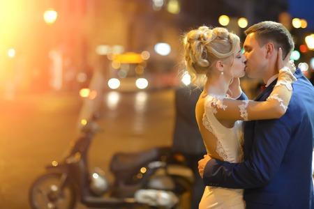 vestido de noche: Encantadora joven pareja de la boda de la mujer rubia de vestido blanco y el hombre en traje azul abrazando y besando en la calle de la ciudad de noche con luces de colores brillantes copyspace al aire libre, horizontal de la imagen
