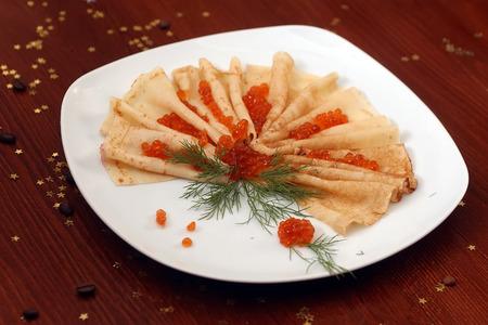 cafe bombon: Porción de cuña con caviar de salmón rojo arriba y el eneldo verde fresco en la placa blanca en la mesa de madera con los granos de café y decorativa estrella de oro el caramelo, horizontal de la imagen Foto de archivo