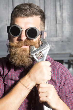 alligator wrench: Poprtrait of young crazy man in purple checkered shirt and aviator glasses standing in garage holding iron metallized spanner near mouth on workshop background, vertical picture