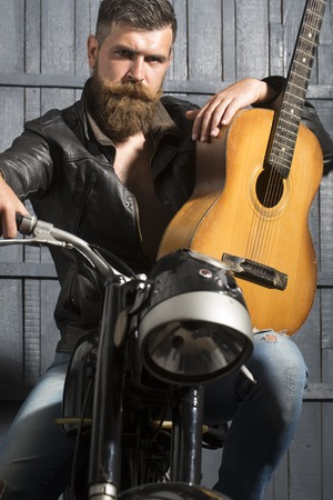 One handsome unshaven musical man with beard and handlebar moustache in leather jacket sitting on motorcycle with acoustic guitar looking forward in garage on wooden wall background, vertical picture
