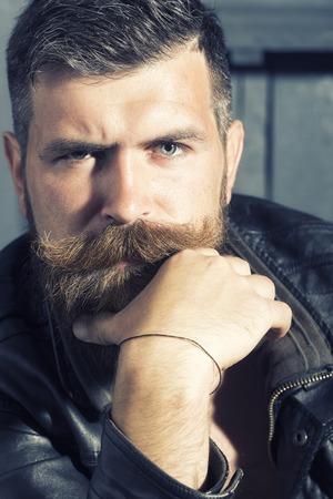 hombres maduros: Retrato de hombre sin afeitar apuesto pensativa con la barba y el bigote del manillar de cuero chaqueta de estar mirando hacia adelante con la pulsera en la mano close-up, imagen vertical Foto de archivo