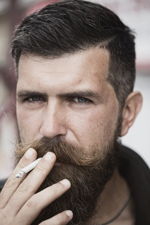 sullen: Portrait of handsome unshaven man with beard and handlebar moustache smoking cigarette looking forward with sullen face outdoor closeup, vertical picture Stock Photo