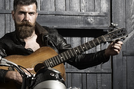Handsome unshaven musical male with beard and handlebar moustache in leather jacket sitting on motorcycle playing acoustic guitar in garage on wooden wall background, horizontal picture Stock fotó