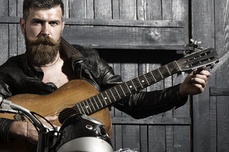 Knap ongeschoren muzikaal mannetje met baard en stuursnor in leerjasjezitting op motorfiets die akoestische gitaar in garage op houten muurachtergrond spelen, horizontaal beeld