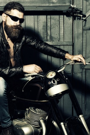 Young sexy cool unshaven biker in leather jacket and sunglasses with long beard and handlebar moustache sitting on motorcycle in garage on wooden wall background, vertical picture