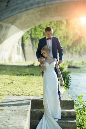 flower bunch: Beautiful young tender wedding couple of blonde woman in long white dress with calla flower bunch and man in blue suit with red bow tie standing under stone bridge on stairs in sunbeam, vertical photo Stock Photo