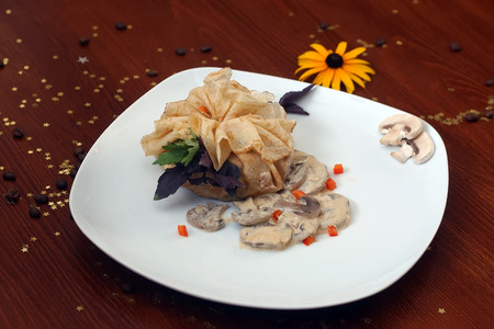 cafe bombon: Stuffed pancake with field mushrooms in sauce with basil and parsley on white plate on wooden table with yellow flower coffee beans and gold star bon-bon, horizontal picture