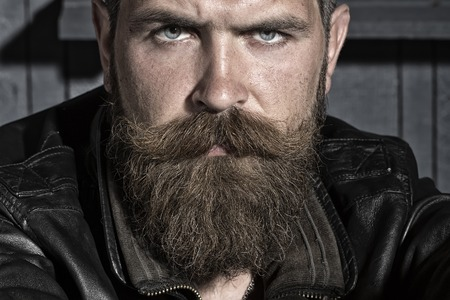 Portrait of handsome sullen unshaven male with long beard and handlebar moustache in black leather jacket sitting looking forward on workshop background, horizontal picture