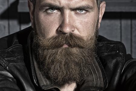 bigote: Retrato del varón hermoso sin afeitar hosca con larga barba y bigote en chaqueta de cuero negro que se sienta mirando hacia adelante en el fondo del taller, cuadro horizontal Foto de archivo