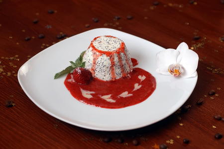 cafe bombon: Dessert of white with black seeds dragonfruit pulp drizzled with berry red jam strawberry mint leaves on plate on wood table with orchid coffee beans and decorative gold star bon-bon, horizontal photo