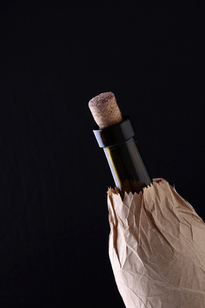 corked: Closeup of one glass green wine corked bottle with alcohol beverage with cork in brown paper packet isolated on black studio background copyspace, vertical picture Stock Photo