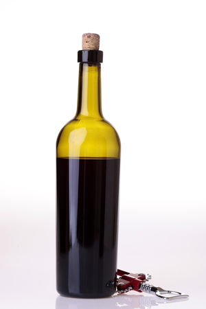 corked: One green glass bottle with red wine and corkscrew standing isolated on white reflecting table top background copyspace, vertical picture Stock Photo