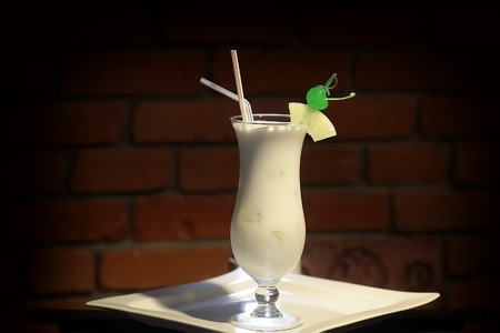 juice: Glass with alcoholic pina colada cocktail of light rum coir coconut milk crushed ice frappe pineapple juice and slice green cherry and drink straws on white plate on brick background, horizontal photo