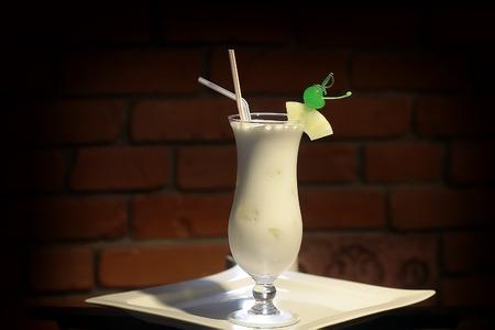 coco: Vidrio con alcohol c�ctel pi�a colada de ron blanco leche de coco coco hielo picado frappe de jugo de pi�a y cortar en rodajas verde cereza y bebida pajas en un plato blanco sobre fondo de ladrillo, foto horizontal