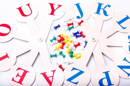 drawingpin: Many colorful drawing-pins of red yellow green blue colors and english alphabet fan with capital letters lying on white school desk background copyspace, horizontal photo