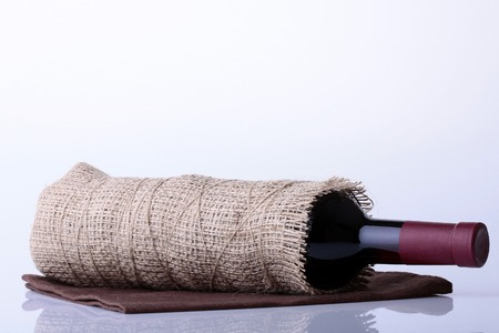 corked: Closeup of one glass green wine corked bottle with alcohol fresh grapes beverage with cork wrapped in burlap fabric lying on brown napkin on white background copyspace, horizontal picture Stock Photo
