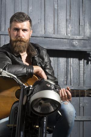 bigote: Hombre atractivo musical sin afeitar, con barba y bigote en la chaqueta de cuero sentado en la motocicleta con la guitarra acústica en el garaje en copyspace pared de madera, imagen vertical Foto de archivo