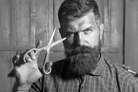 Portrait of unshaven boy in checkered shirt with long beard and handlebar moustache showing sharp scissors looking forward standing on wooden wall black and white, horizontal picture