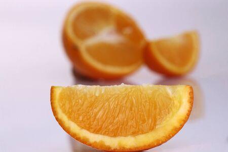 lobule: Closeup of fresh juisy bright tasty orange lobule on blur background of half of citrus fruit lying on white reflecting table top in studio, horizontal picture