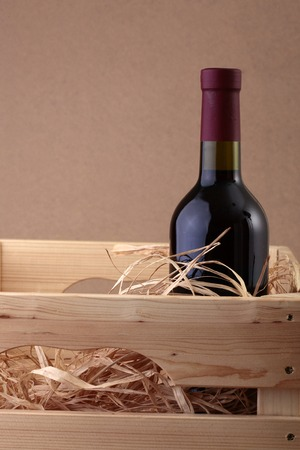 corked: One glass wine corked new bottle full of alcohol red beverage wrapped in straw standing in wooden box on paper background copyspace, vertical picture