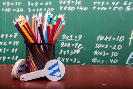 math set: Colorful pencils of red yellow orange violet purple pink green and blue in stationary cup ruler and fan english alphabet standing on brown school desk on written with white chalk blackboard on math Stock Photo