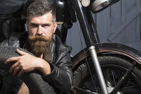 Handsome unshaven male biker in leather jacket sitting near motorcycle in garage with big black rubber spare wheel looking forward on wooden wall , horizontal picture Stock Photo