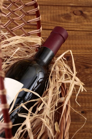 corked: One glass wine corked new bottle full of alcohol red beverage wrapped in straw lying in wattled basket on wooden background closeup, vertical picture