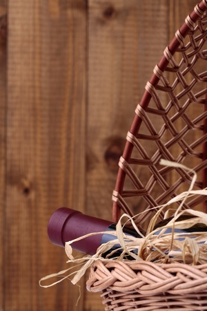corked: One glass wine corked new bottle full of alcohol red beverage wrapped in straw lying in wattled basket on wooden background copyspace, vertical picture