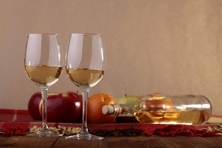 glass bottles: Many fresh ripe red apples and orange fruits with glassy bottle lying on checkered plaid near two goblets with white wine standing on wooden table top on paper background copyspace, horizontal picture Stock Photo