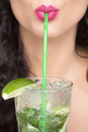 Close-up van seksuele mooie brunette vrouwelijk gezicht van het meisje met krullend haar en roze lippen drinken van alcoholische mojito cocktail van mint soda lichte rum en kalk met stro, verticale foto