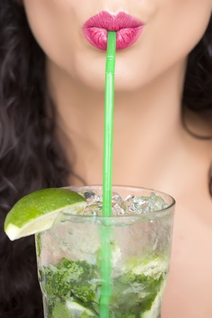 drinking soda: Closeup of sexual pretty brunette female face of girl with curly hair and pink lips drinking alcoholic mojito cocktail from mint soda light rum and lime with straw, vertical picture