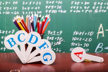 matematicas: Lápices de colores de rojo naranja violeta rosa púrpura verde y azul en la regla taza fija y ventilador alfabeto Inglés de pie en la escuela escritorio marrón en escritos con tiza en la pizarra blanca matemáticas