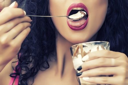 Closeup of sexual attractive female face of brunette lady with curly hair and open mouth eating cold dessert of ice cream and coffe glissade from glass with spoon, horizontal picture Standard-Bild
