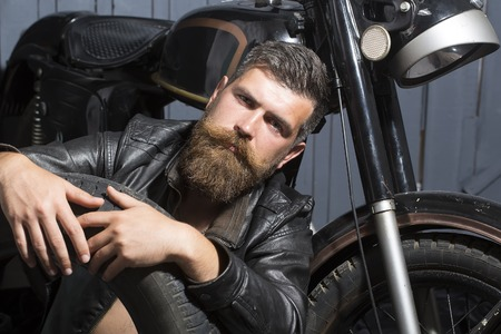 stylish hair: Attractive unshaven male biker in leather jacket sitting near motorcycle in garage with big black rubber spare wheel looking forward on wooden wall , horizontal picture