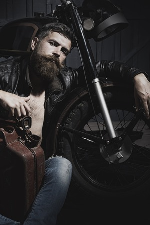 black head and moustache: Handsome unshaven male biker in leather jacket sitting near motorcycle in garage with big brown old rusty fuel can looking forward on workshop , vertical picture Stock Photo