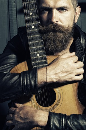 Attractive unshaven musical man with beard and handlebar moustache holding acoustic string guitar with finger-board looking forward indoor on wooden wall black and white, vertical picture
