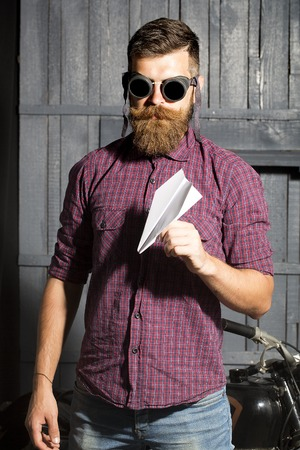 male facial: Attractive unshaven male biker in purple checkered shirt and glasses standing near motorbike in garage holding white paper plane looking forward on workshop , vertical picture Stock Photo