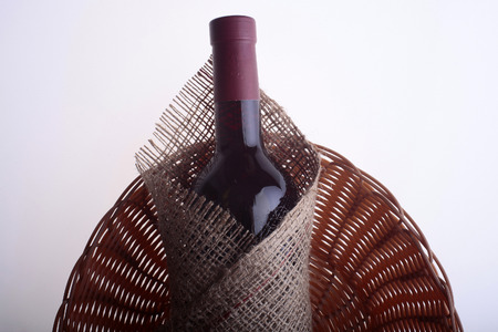 corked: Closeup of one glass green wine corked bottle with alcohol fresh grapes beverage with cork wrapped in burlap fabric lying on wattled napkin on white background copyspace, horizontal picture Stock Photo