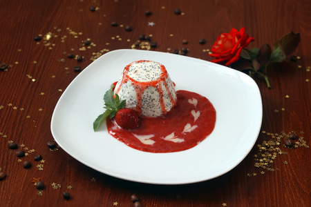 cafe bombon: Dessert of white with black seeds dragonfruit pulp drizzled with berry red jam strawberry mint leaves on plate on wooden table with rose coffee beans and decorative gold star bon-bon, horizontal photo Foto de archivo