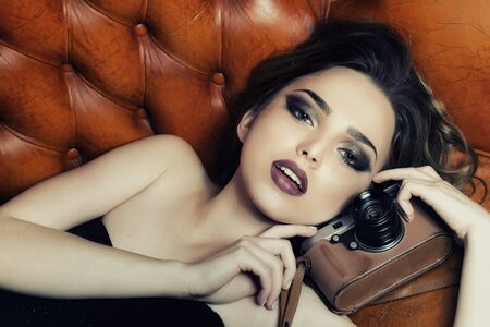 beauty face: Portrait of stylish sexual young lady with bright makeup in black dress without shoulder-straps looking forward lying on leather brown royal sofa holding photographic camera, horizontal picture