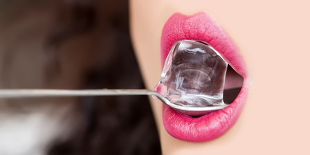 cubes: Closeup of sexy open female mouth of beautiful young woman with bright pink lips tasting cold fresh crystal ice cube on silver colour long spoon, horizontal picture