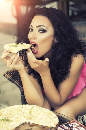 sexy girl sitting: Sensual beautiful brunette lady with curly hair and bright makeup in pink clothes sitting in cafe outdoor eating hot delicious pizza with hands, vertical picture