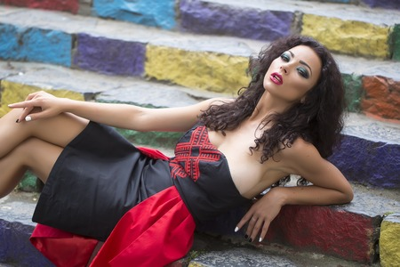 busty: Joven chica morena tetona sexual atractiva con el pelo rizado en vestido negro y rojo que se sienta en las escaleras de colores azul violeta naranja yellowe y colores verdes al aire libre, horizontal de la imagen