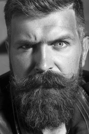 bigote: Primer de la cara sin afeitar emocional serio masculino guapo con larga barba y bigote mirando hacia adelante en el fondo taller de blanco y negro, imagen vertical